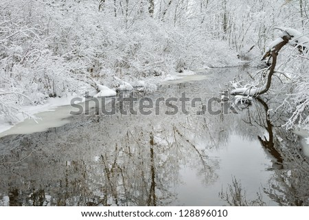Winter creek framed by snow flocked trees and with reflections in calm water, Michigan, USA - stock photo