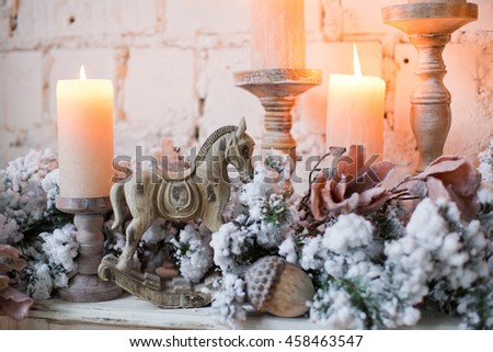 winter decor with candles, wooden horse and spruce branches