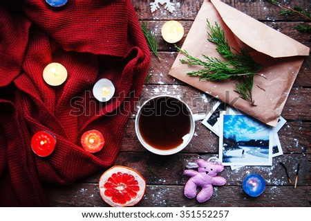 Winter decoration. Composition on wood background. Warm scarf, hot tea, candles, greeting cards, photographs, cut grapefruit. Christmas. Christmas mood. Christmas spirit. Fir branches.