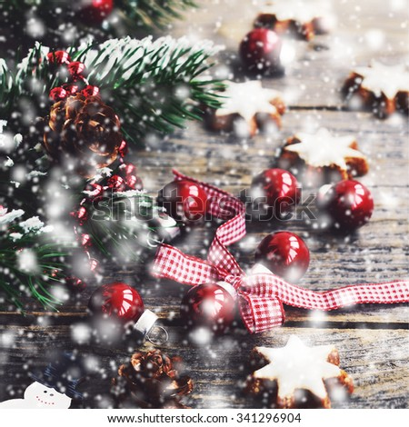 Winter decoration with christmas red balls, gingerbread cookies and falling snow - stock photo