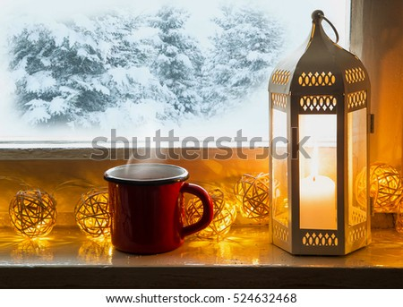 Winter decoration with lantern, hot chocolate cup and lights on windowsill