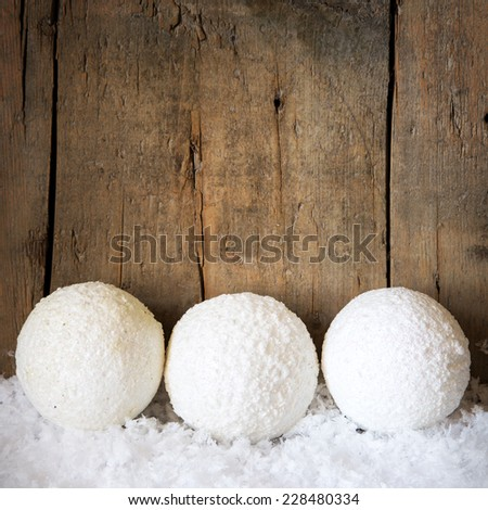 winter decoration with three snowballs, wooden background - stock photo