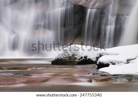 Winter detail of cascade and snowy boulders below waterfall. Wavy water level.. Stream in deep freeze. - stock photo