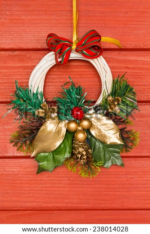 Winter door or window decoration with ribbon, evergreen and berries on a red wooden background.
