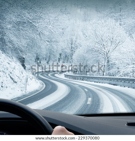Winter Driving - Curvy Snowy Country Road - Curvy snowy country road leading through a mountain landscape. - stock photo