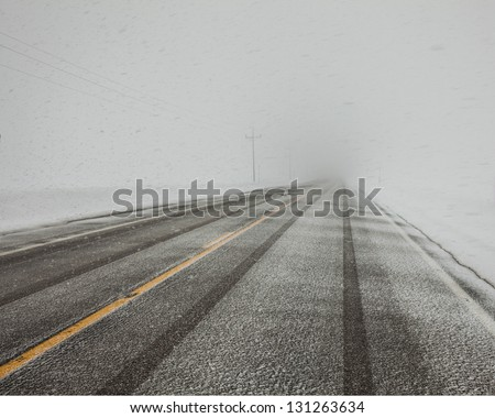 WInter driving in blowing snow in eastern Idaho.  Ice on the pavement. - stock photo