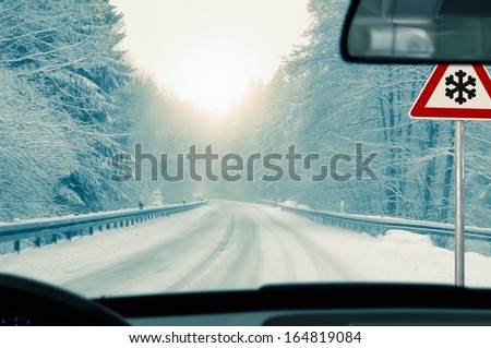 winter driving - snowy country road driving in winter - snowy country road and warning sign: risk of snow and ice - stock photo