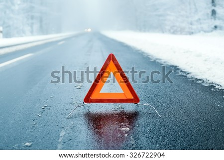 Winter Driving  - Warning triangle on a winter road - stock photo