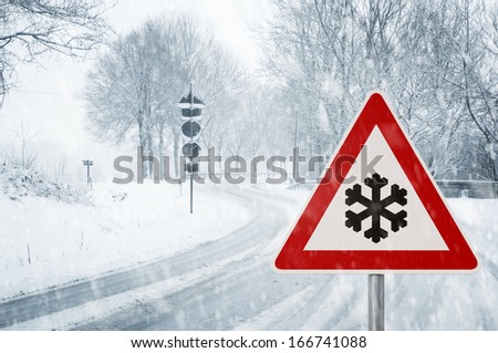 winter driving - winding country road in winter - risk of snow and ice - stock photo