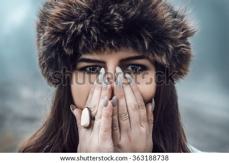 Winter emotional portrait of young beautiful woman covering her mouth. Model looking at camera. Lady wearing stylish furry hat. - stock photo