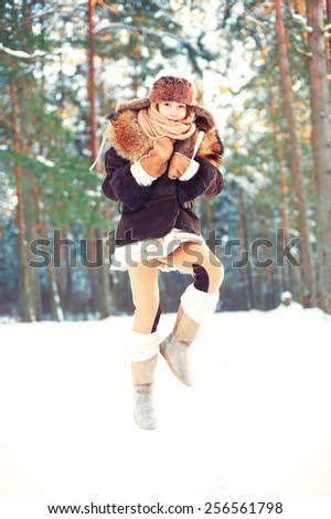 Winter enjoyment. Cheerful girl having fun in forest. Outdoors. Filtered image. - stock photo