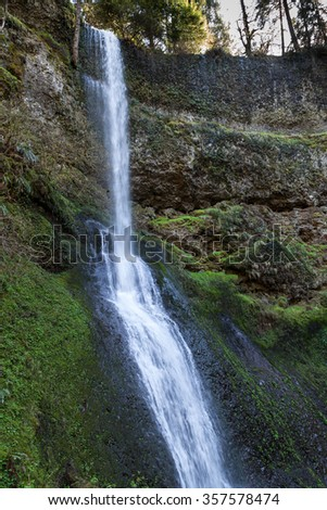 Winter Falls located in Silver Falls State Park in Oregon flowing over rock and moss in springtime. - stock photo