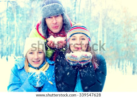 Winter Family Outdoors. Happy Joyful Family with kid blowing Snow. Wintertime, winter fun - stock photo