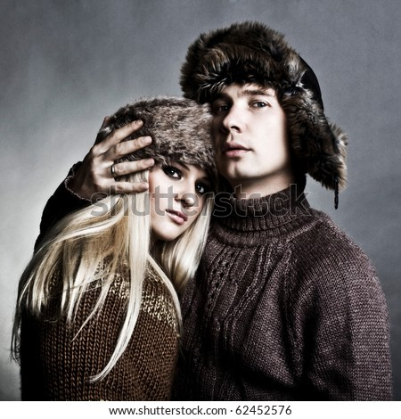 Winter fashion beautiful man and woman studio photo shooting - stock photo