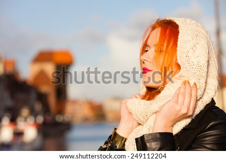 Winter fashion. Beauty face portrait redhaired young woman in warm clothing outdoor enjoying sunlight on sunny day. - stock photo