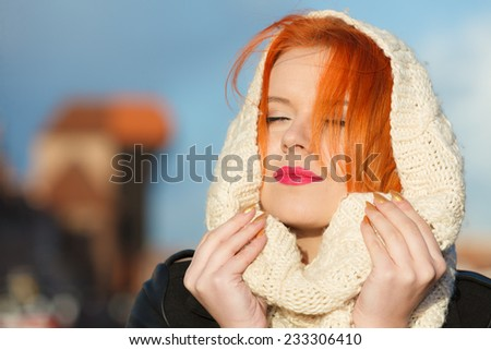 Winter fashion. Beauty girl portrait red hair young woman in warm clothing outdoor enjoying sunlight on sunny day. City Gdansk in the background - stock photo