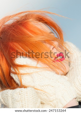 Winter fashion. Beauty redhaired head with hair blowing on wind, woman in warm clothing outdoor enjoying sunlight. - stock photo