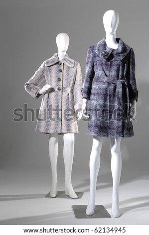 Winter fashion coat dress on mannequin in gray background - stock photo