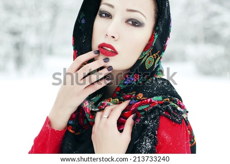 Winter fashion concept. Portrait of young woman in red cardigan and russian kerchief posing in the park. Snowflakes on lashes. Perfect make-up. Close up. Vogue style. Outdoor shot - stock photo