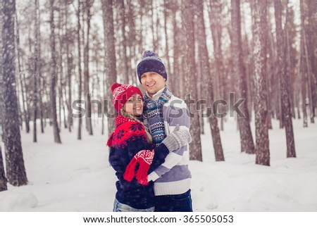 winter, fashion, couple concept - smiling man and woman in hats and scarf hugging over forest background.