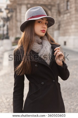 Winter fashion street portrait of a gorgeous young brunette woman.