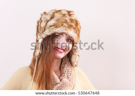 Winter fashion. Young smiling woman wearing fashionable wintertime clothes fur cap studio shot on gray