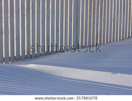 Winter fence, snow and shadow. - stock photo