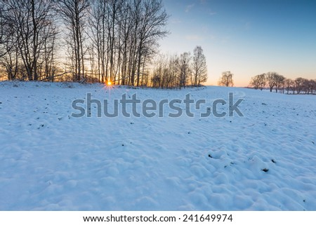 winter field sunset. countryside under snow - stock photo