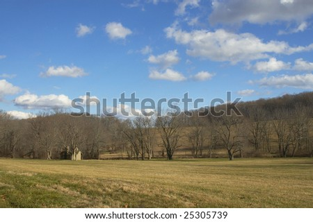Winter field with small stone house amongst barren trees. Blue sky, white clouds. - stock photo