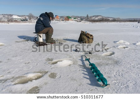 Winter fisherman on the river ice