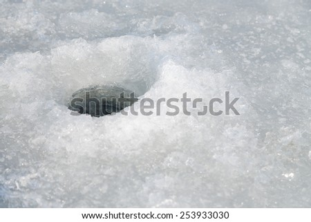 Winter fishing. Ice fishing. Fisherman on ice fishing from the well, a special winter fishing rod. Fishing in winter. Active, cold, fish, winter fishing tackle. Sport winter fishing/ - stock photo