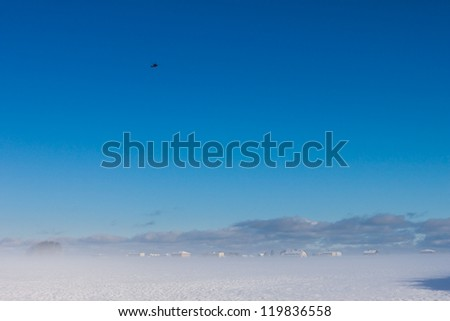 winter foggy landscape with helicopter in the sky