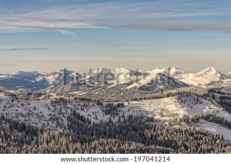 Winter forest on mountain range in French Alps - stock photo