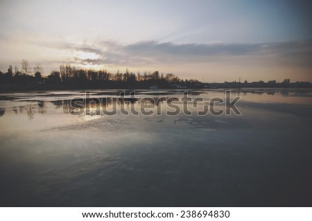 winter frozen evening lake in the city park - stock photo