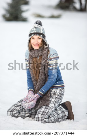 Winter fun. Happy young woman playing with snow in park enjoy her winter vacation