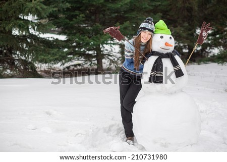 Winter fun, happy young woman playing with snowman - stock photo