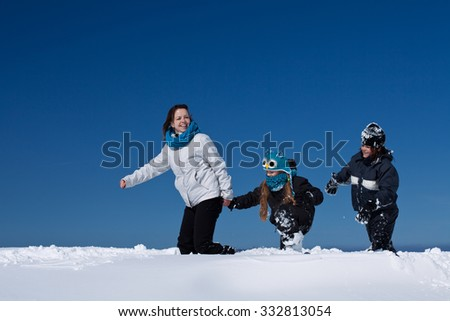 Winter fun in the deep snow - family enjoying the walk on a sunny winter day, with copy space - stock photo