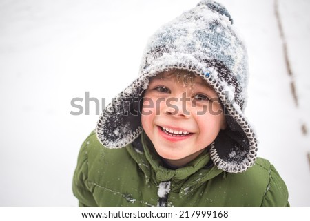 Winter fun, kid winter playing -cute boy has a fun in snow - stock photo
