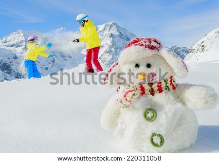 Winter fun, snowman and happy skiers - stock photo
