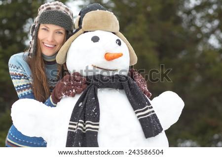 Winter fun, winter joy, winter vacation - beautiful woman with snowman. focus on woman - stock photo