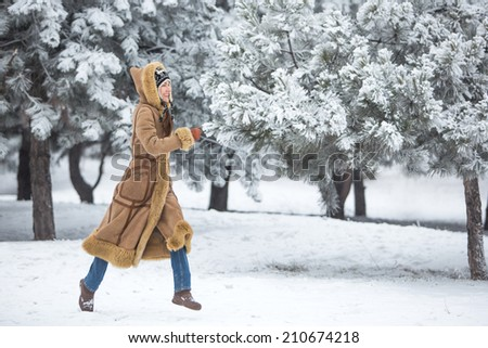 Winter fun, winter leisure, winter holiday. Young winter woman running in winter park. motion - stock photo