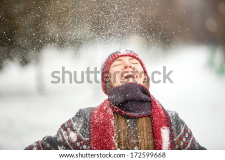 Winter fun woman playful during winter holidays vacation outside in snow forest. Romantic young woman enjoy snowfall with closed eyes - stock photo