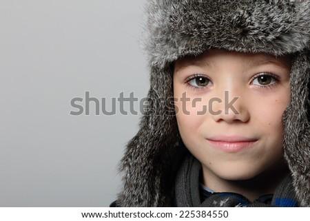 Winter fur hat clothing boy on grey background - stock photo