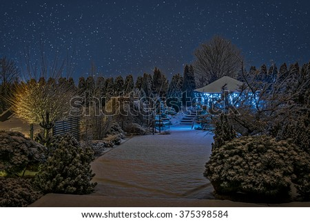 Winter garden shot by night with Christmas lights hanging down the gazebo - stock photo