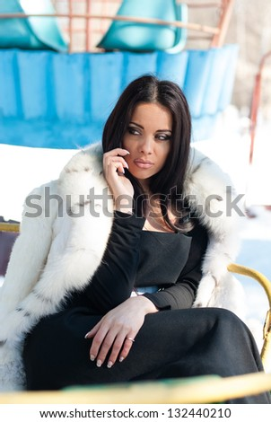 Winter Girl in Luxury Fashion Fur Coat on mobile phone - stock photo