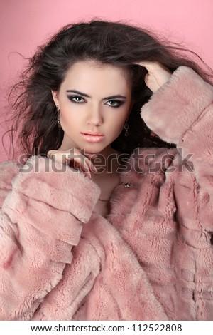Winter Girl in Luxury Fur Coat over pink - stock photo
