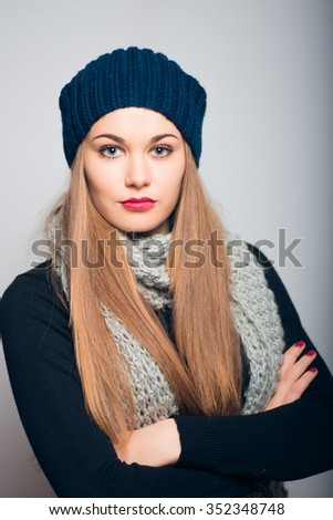 Winter girl waiting for something with his arms crossed. Lifestyle studio photo isolated portrait of a woman on a gray background.