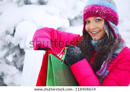 winter girl with gift bags on snow background - stock photo