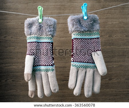 winter gloves hanging on a clothes line rope with wooden background