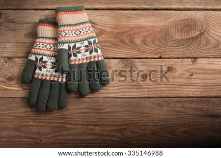 winter gloves on wooden background - stock photo